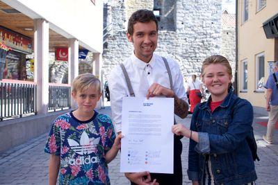 Barncanceröverlevarna Axel, Isak och Freja med det dokument som alla de närvarande riksdagspartierna skrev under, ett löfte om en särskild satsning på barncancervården. Foto: Robin Wilhelmsson