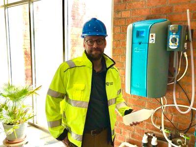 Bild: Marcus Mattson, affärsenhetschef på Gärstadverket, framför maskinen som nu tillverkar desinfektionsmedel.