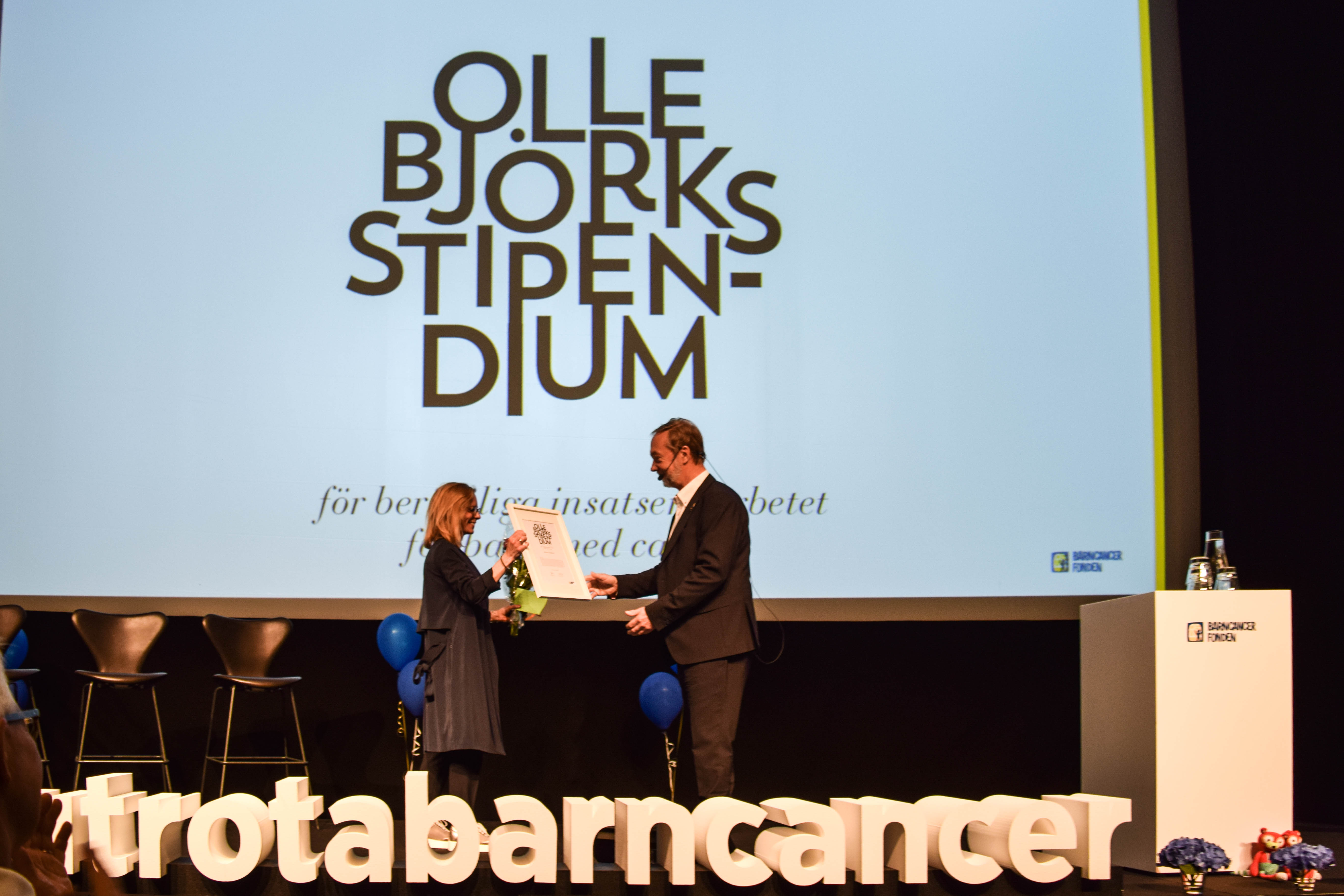 Johanna Hoffstedt tar emot stipendiet av Olle Björk vid Barncancerfondens årsmöte. Foto: Hans Kullin